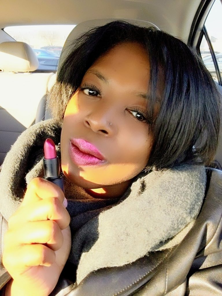 Girl holding pink lipstick while in the car